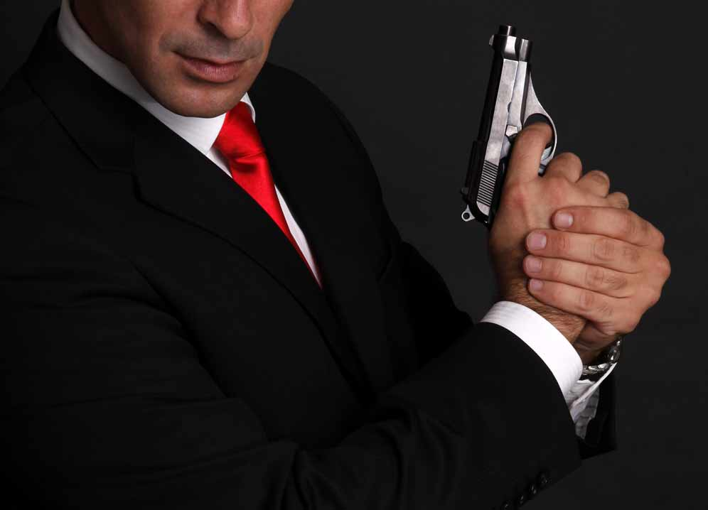 bel homme costume cravate rouge avec une arme james bond