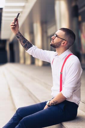 homme d'affaire vetu d'une chemise cravate et bretelles qui prend une photo de lui