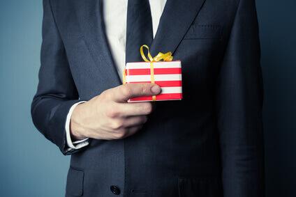 Homme d'affaires en costume cravate avec un cadeau à la main