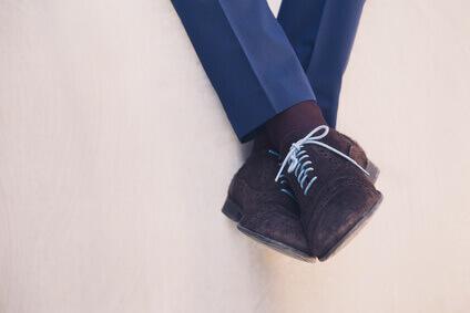 Les jambes d'Homme d'affaires avec chaussures assis sur mur métallique