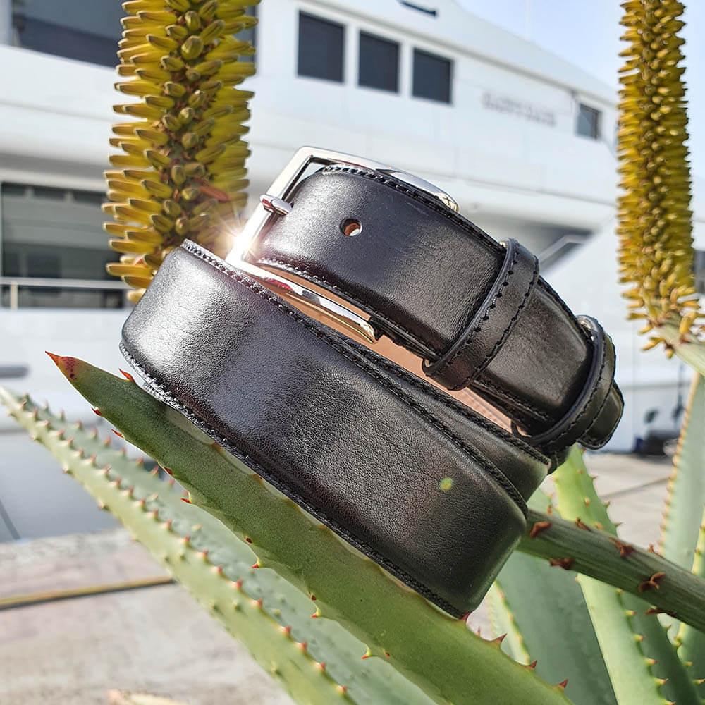 ceinture luxe en cuir noir devant un yacht blanc