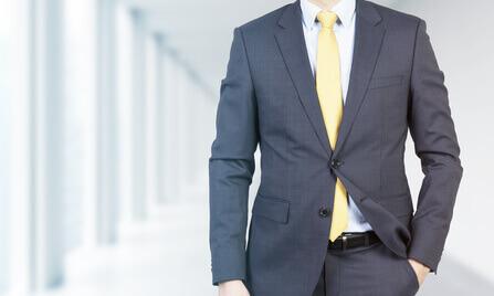 Gros plan d'un professionnel dans costume(procès) formel de la main dans la poche. Bureau(fonctions) moderne brillant dans tache sur le contexte(la formation).