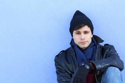 Homme détendu drôle dans vêtements d'hiver isolés sur fond bleu