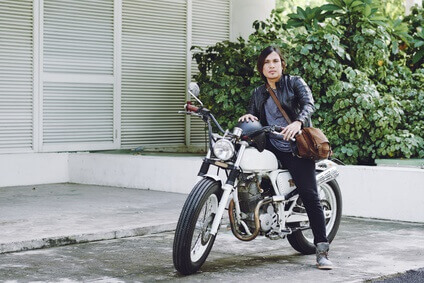 Handsome Asian man wearing stylish clothes sitting on vintage motorcycle and looking at camera, facade of garage on background, full length portrait
