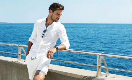 Bel homme portant vêtements blancs posant dans paysage de mer