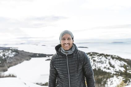 Homme joyeux attendant dehors avec une veste d'hiver