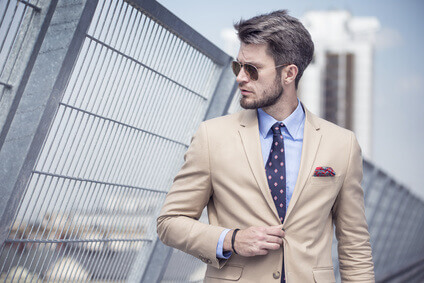 Homme élégant en costume beige et cravate dans la ville