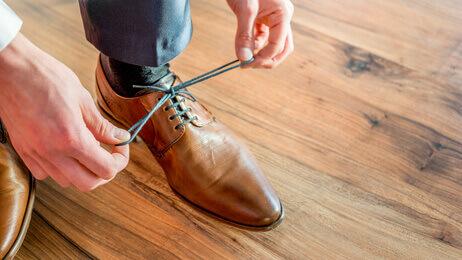 Des lacets sont attachés par un homme daffaires faisant un noeud, une boucle