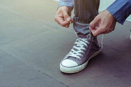 Le bel homme daffaires sassied portant des chaussures et met des lacets sur ses chaussures