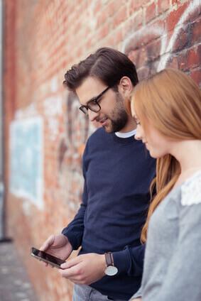Le jeune accouple dans la ville regarde un portable