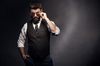 Le portrait de studio de bel homme séduisant(attractif) avec des cheveux bruns, la moustache et la barbe dans la chemise blanche, la cravate