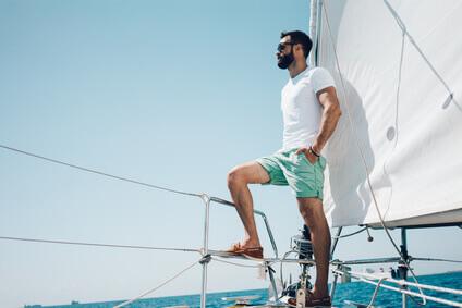 jeune homme barbu étant debout sur le yacht de nez