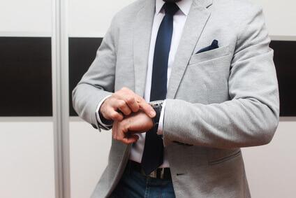 Homme en costume gris avec cravate, pince à cravate et pochette