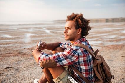 Homme songeur avec sac à dos étant assis et regardant l'horizon