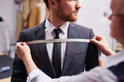 Portrait d'un tailleur qui adapte le costume et prend les mesures
