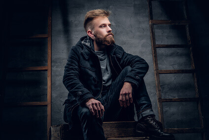 Portrait of urban bearded male dressed in a black jacket.