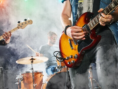 Rock band performs on stage- Guitarist, bass guitar and drums- Guitarist in the foreground- Close-up