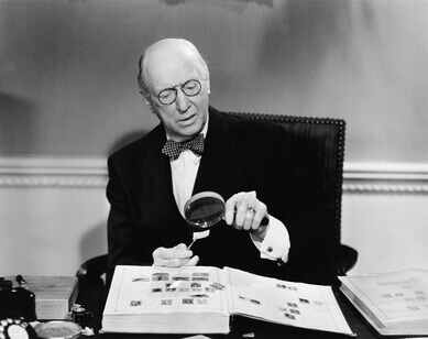 Senior man examining a postage stamp with a magnifying glass - Homme senior examinant un timbre poste avec un verre grossissant