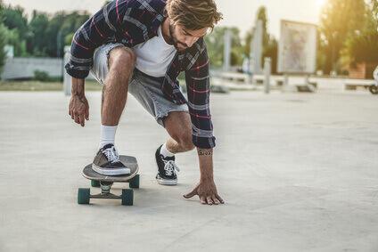 Tattoo skater performing with longboard at sunset in urban city square - Tatouez le patineur fonctionnant(se produisant) avec longboard au coucher du soleil dans la place(le carré) urbaine de la ville