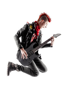 Wild teen boy with red haired mohawk playing guitar while jumping