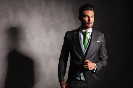 elegant man in tuxedo jacket buttoning his coat looks away