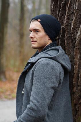 homme seul en manteau qui attend près d'un arbre