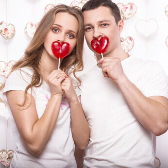 young, beautiful woman and man in love on Valentines Day with candy, Laughing Happy Lovers, showing different poses